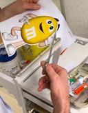 Een verpleegkundige van een Belgisch ziekenhuis vrolijkt het infuus op voor een ziek, angstig kind.