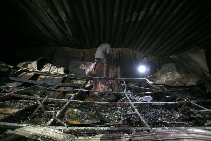 Mensen meten de schade op bij het afgebrande Al-Hussein-ziekenhuis in Nasiriya.