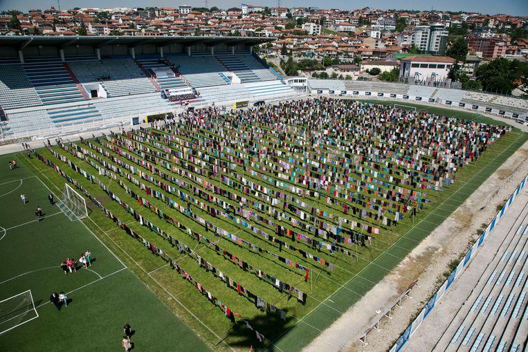 De duizenden jurken en rokken aan waslijnen in het stadion van Pristina, een installatie van kunstenaar en activist Alketa Xhafa Mripa, brengen de naar schatting 20.000 verkrachtingsslachtoffers in de oorlog van Kosovo tegen Servië in beeld. Beeld AP
