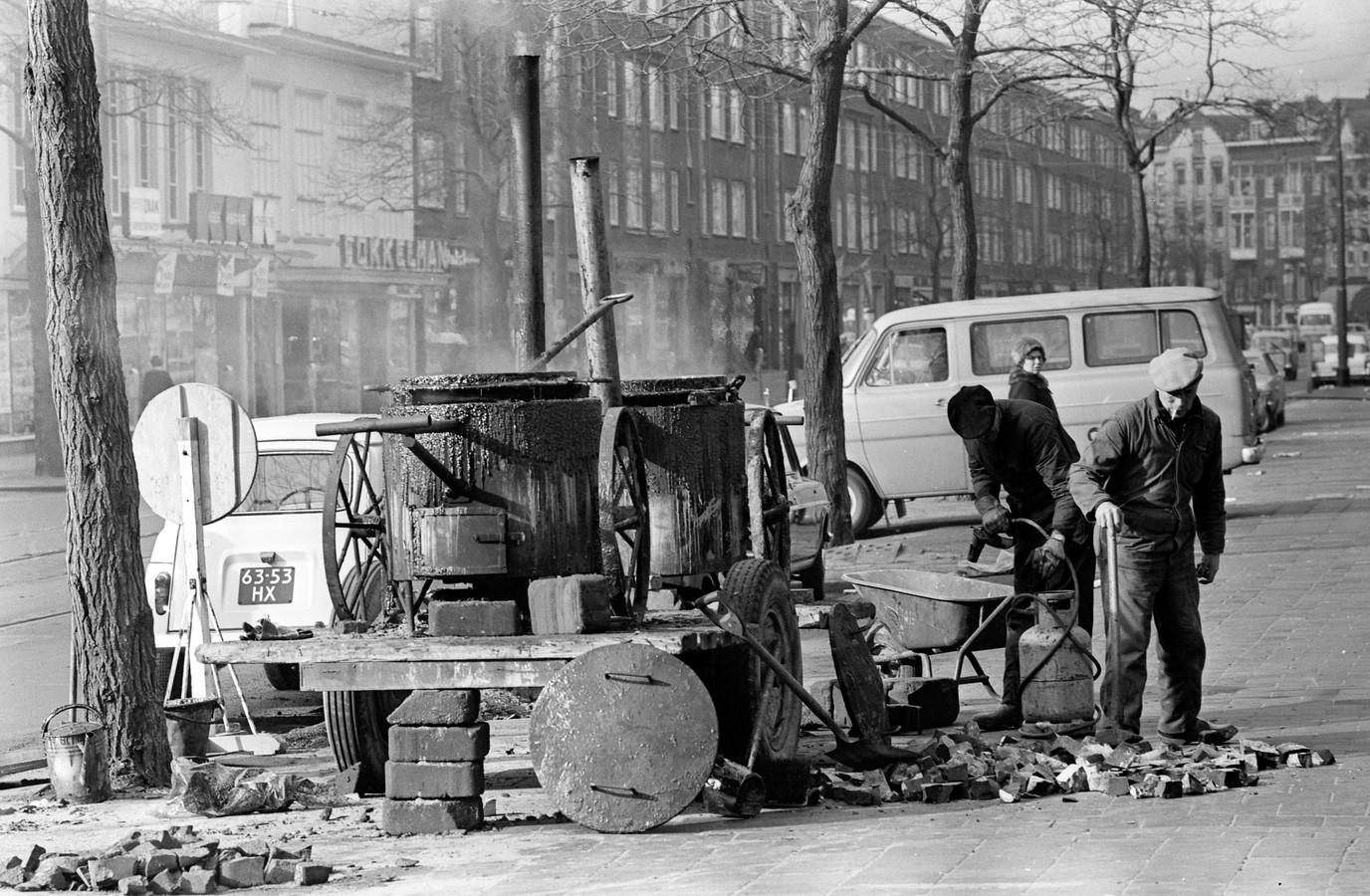 Ketels vol vloeibare teer op de Nieuwe Binnenweg, klaar om tussen de klinkers te worden gegoten.
