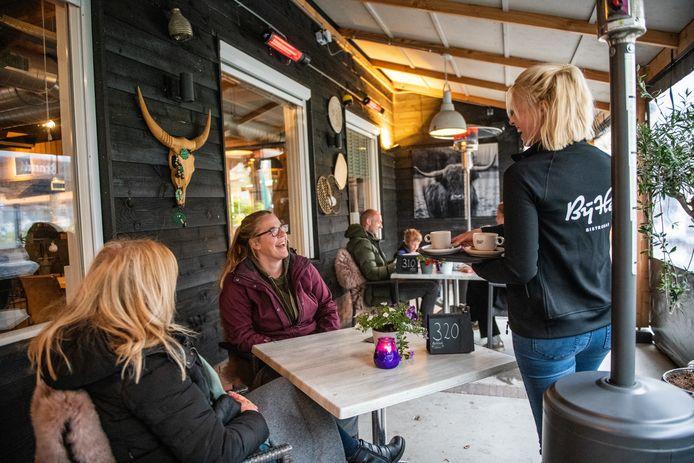 Brigitte (links) en Nicole genieten ervan dat de horeca weer open is, zij zitten vanwege het slechte weer aan het begin van de donderdagmiddag op het overdekte terras bij Bij Hen in Alphen.