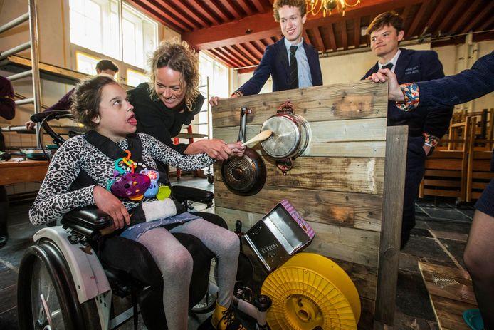 Studenten werken aan het speelbord voor het kinderdagverblijf Aandachtslab in Rijswijk. Maud en haar gehandicapte dochter testen een paneel.