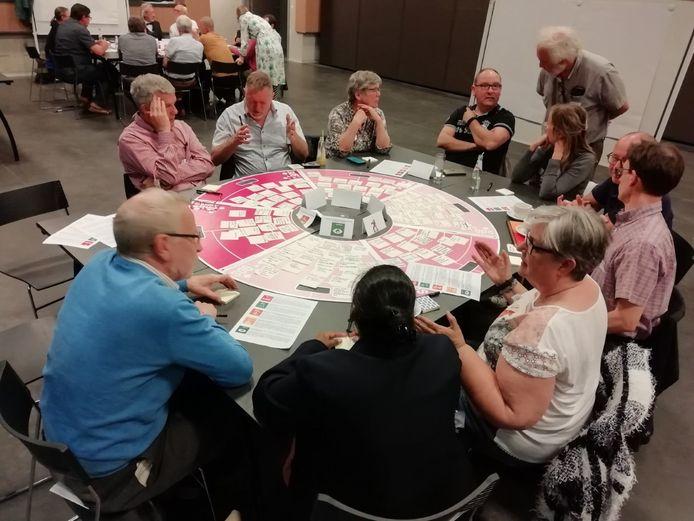 De deelnemers zaten rond tafels waar je ideeën  op de schijf met vijf thema's kon plakken.