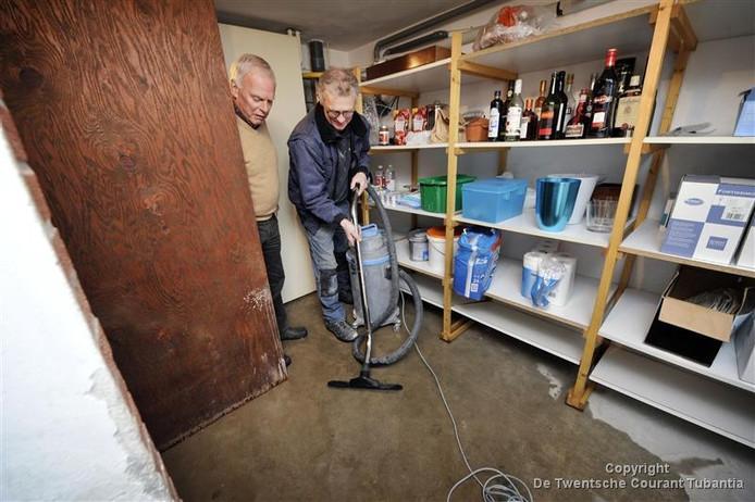 Voormalig huisarts Jacques Vermeulen krijgt in zijn woning aan de Jan Janstraat in Oldenzaal hulp van installateur Ben Kleisman die met een waterstofzuiger water uit de kelder wegzuigt.