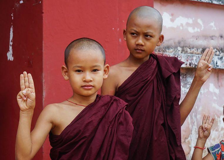 Jonge boeddhistische monniken in opleiding houden drie vingers omhoog, een gebaar om de demonstranten tegen de staatsgreep te steunen. Beeld AFP