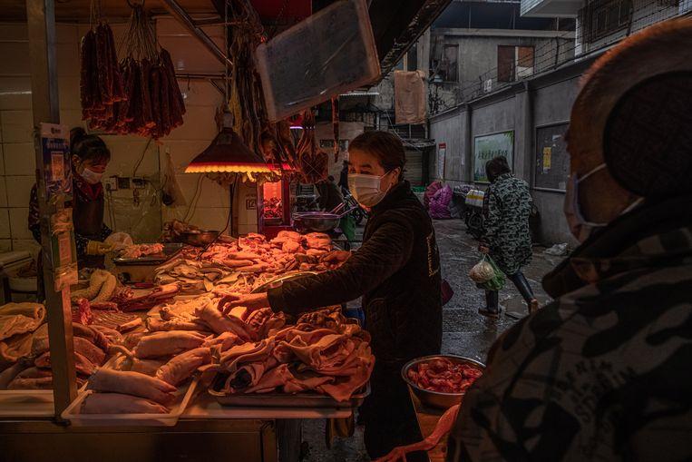 Een marktkoopvrouw tussen de varkenspoten en ander vlees in Wuhan. Beeld EPA
