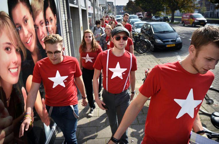 Leden van Rood, de jeugdafdeling van de SP, zijn in september 2017 bezig met ouderwets flyeren en handtekeningen verzamelen in Den Haag. Beeld Marcel van den Bergh / de Volkskrant