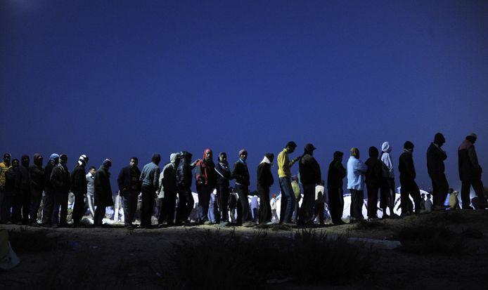 Uit Libië gevluchte migranten in de rij in een vluchtelingenkamp in Tunesië. Archieffoto uit 2011.