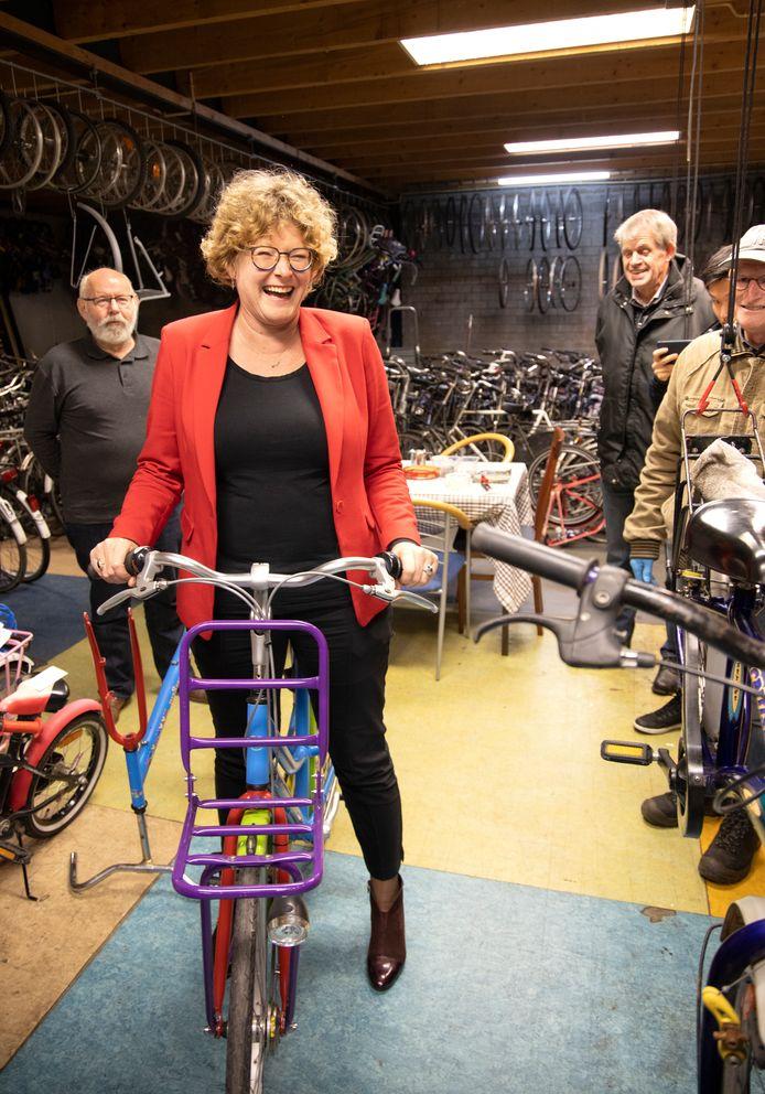 Wethouder Greet Buter krijgt een fiets overhandigd van Stichting Leergeld.