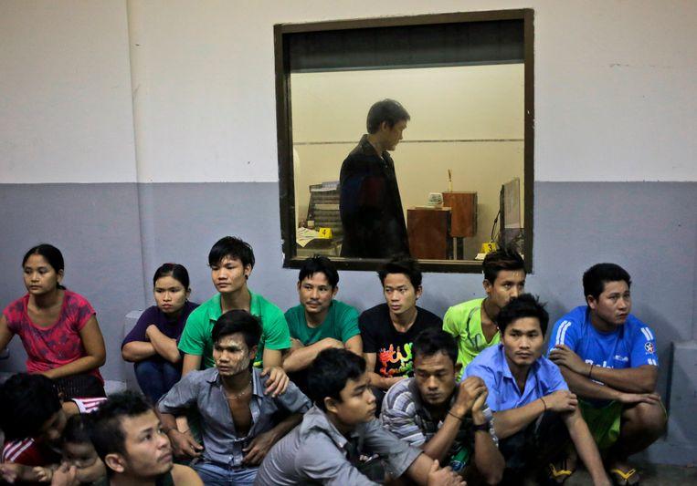 Arbeiders wachten tijdens een inval van de autoriteiten in een garnaalfabriek. Beeld AP