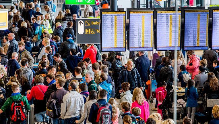 Reizigers wachten in rijen voor de check-ins en security check op luchthaven Schiphol. Beeld anp