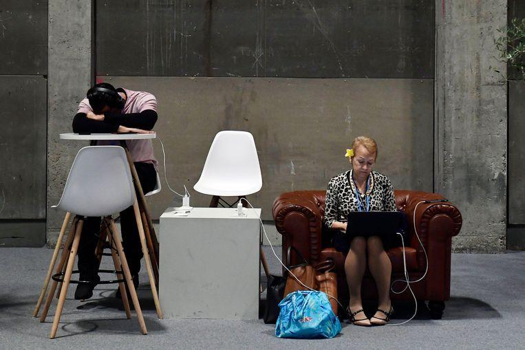 Twee bezoekers van de klimaattop in Madrid laden hun elektronica op. Beeld AFP