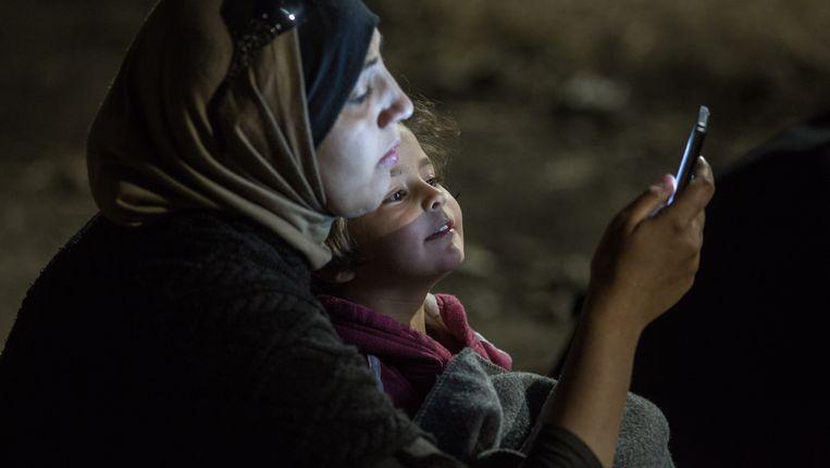 Een meisje kijkt naar haar moeders smartphone in het Hongaarse Roszke. Beeld GETTY