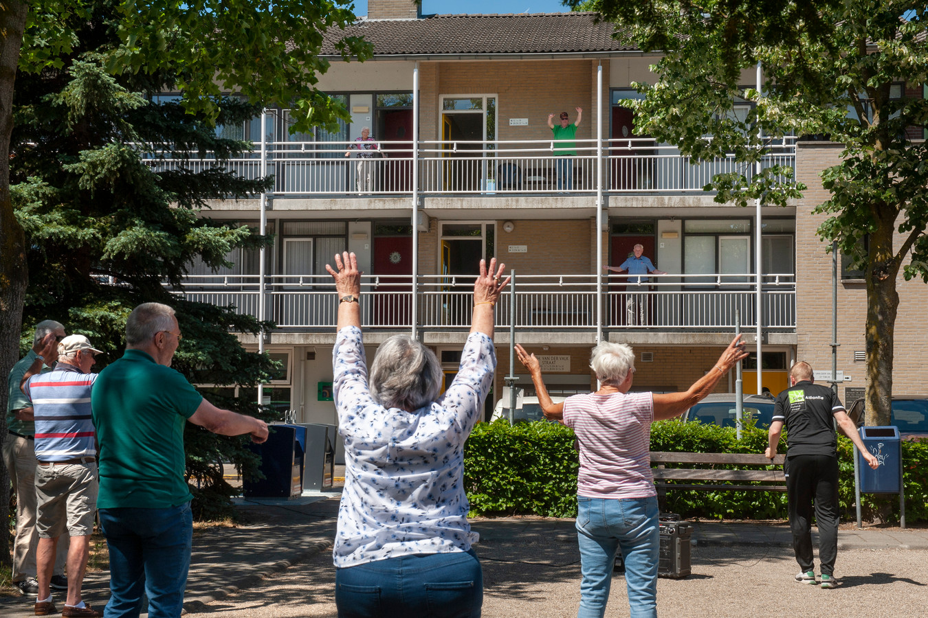 De senioren van jeu-de-boules club 'De Actieven' bewegen mee met de ouderen op de galerij van het appartementencomplex in Rosmalen