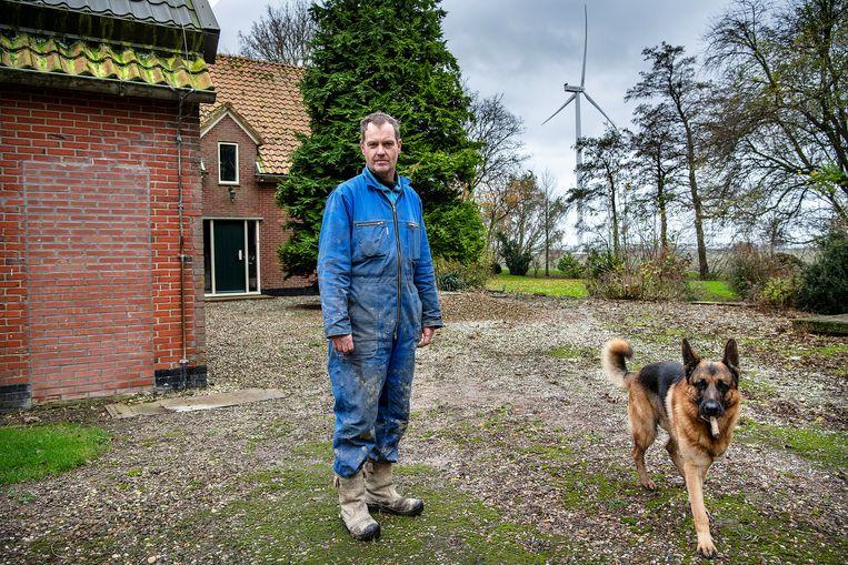 Akkerbouwer Ad Haverkamp met zijn hond Rex bij de windmolens in Middenmeer. Beeld Guus Dubbelman / de Volkskrant