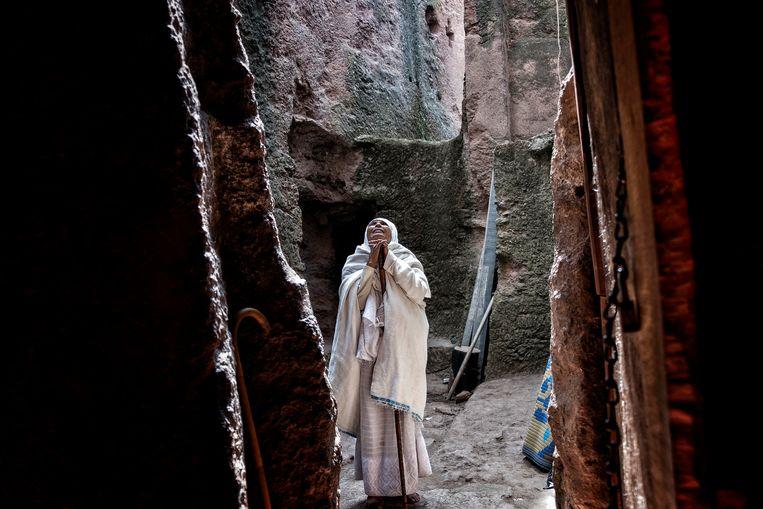 Een vrouw bidt bij de ingang van een van de historische kerken in Lalibela. Beeld LightRocket via Getty Images