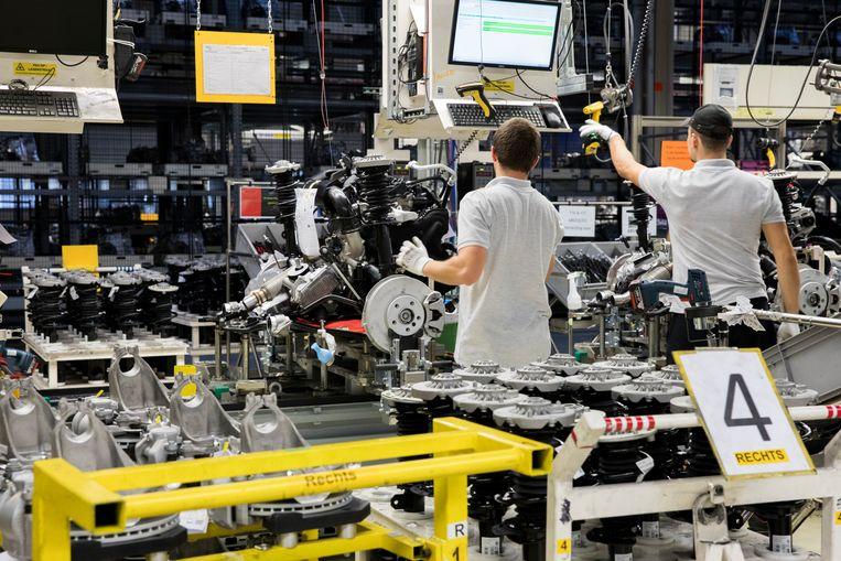 Medewerkers bij een assemblagelijn van autofabrikant VDL Nedcar in Born.  Beeld ANP