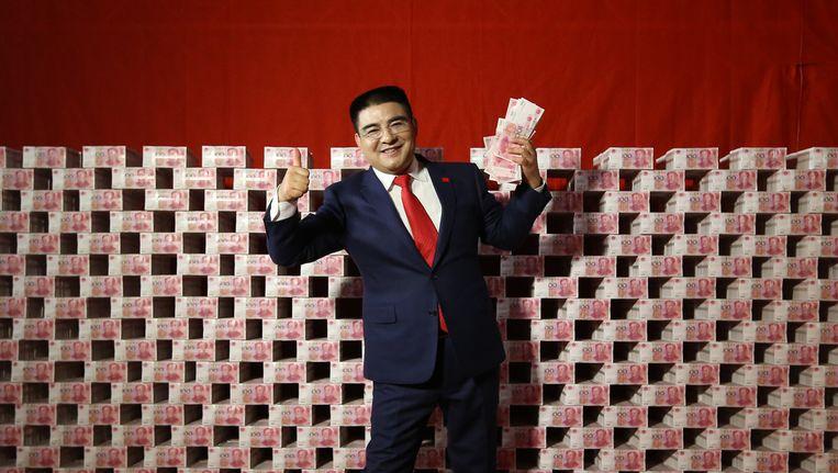 Chen Guangbiao poseert in een televisiestudio voor stapels biljetten van 100 yuan om de National Ecomic Census te promoten. Beeld ChinaFotoPress via Getty Images
