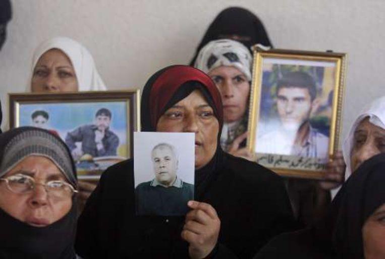 Palestijnse vrouwen houden foto's vast van familieleden die achter Israëlische tralies zitten, maar mogelijk in de komende twee weken vrijkomen. Beeld UNKNOWN