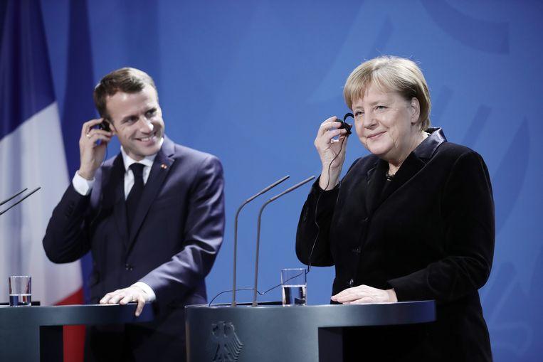 De Franse president Emmanuel Macron had een zeer ambitieuze begroting voor ogen, maar dat was zonder Duitsland gerekend, dat gekant is tegen elke vorm van het herverdelen van de schulden. Op de foto links de Franse president Macron en rechts de Duitse Bondskanselier Merkel. Beeld Michael Kappeler/dpa