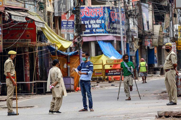 Een man toont zijn doktersvoorschrift aan agenten tijdens hun patrouille in Allahabad.