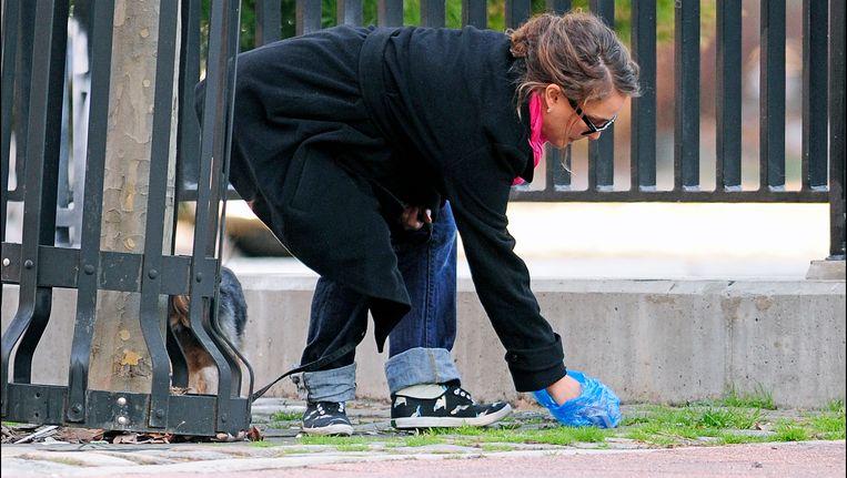 De Amerikaanse actrice Natalie Portman raapt de poep van haar hond op. Beeld photo_news