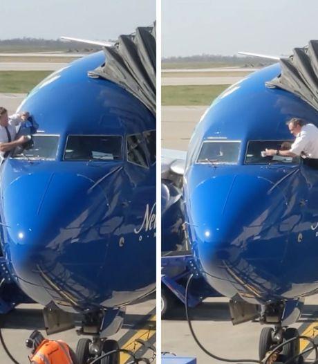 Des pilotes de ligne nettoient le pare-brise de leur avion avant de décoller
