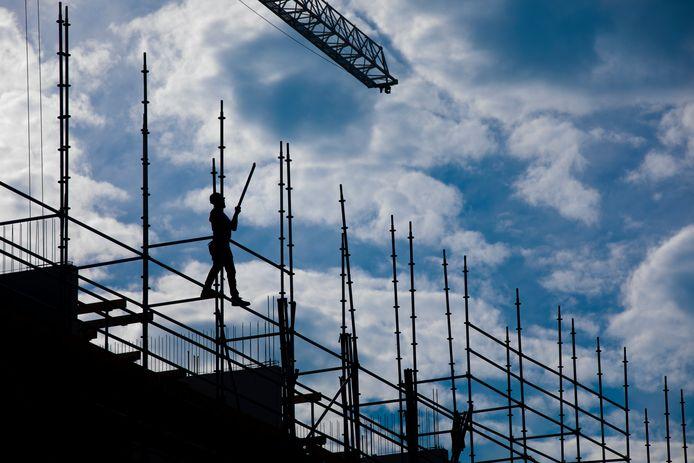 Een bouwvakker aan het werk op een bouwplaats in de Amsterdamse wijk Westlandgracht.