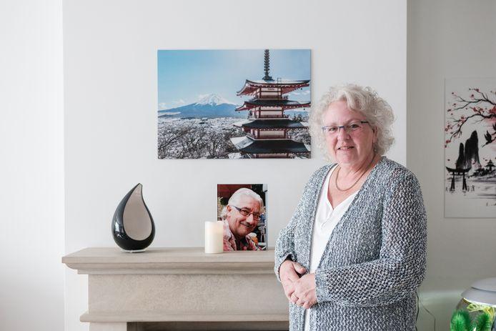 Wilma Kolkman bij foto en urn van haar overleden man.