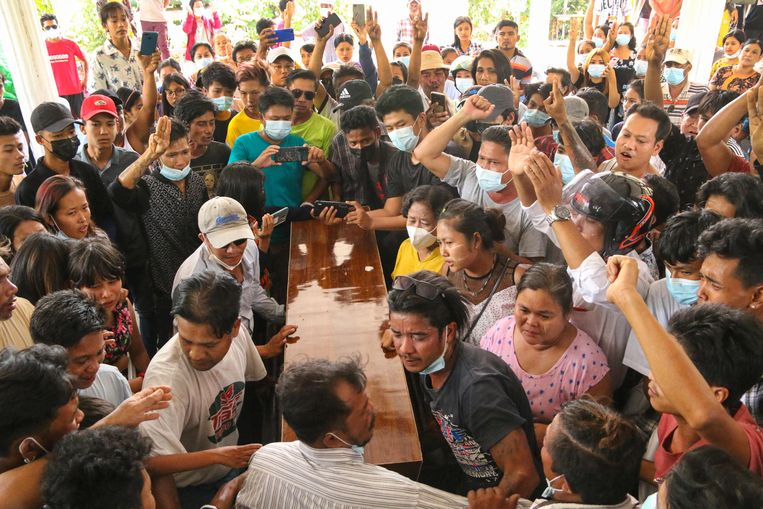Mensen rouwen bij de kist van een doodgeschoten demonstrant in Myanmar. Beeld AFP