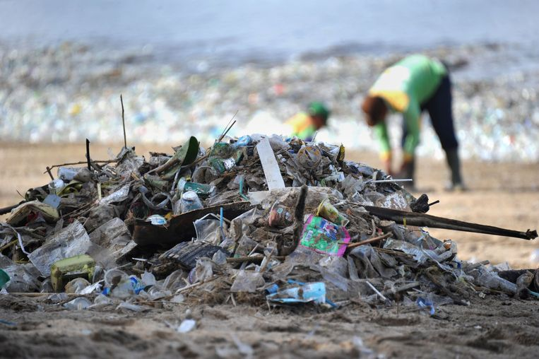 This photo taken on December 19, 2017 shows rubbish collectors picking up trash on Kuta beach near Denpasar, on Indonesia's tourist island of Bali. The palm-fringed shoreline of Bali's Kuta beach has long been a favourite with tourists seeking sun and surf, but nowadays its golden shores are being lost under a mountain of garbage. / AFP PHOTO / SONNY TUMBELAKA / TO GO WITH Indonesia-rubbish-Bali-environment,FEATURE by Bagus Saragih Beeld AFP