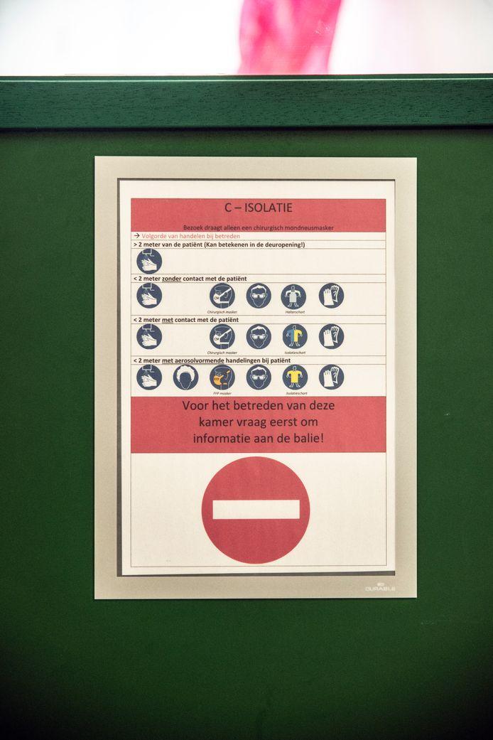 Waarschuwing op de deur van een kamer in het CWZ in Nijmegen met regels voor het betreden van een besmette kamer.