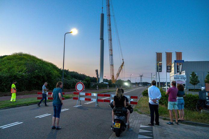 Van een veilige afstand kan publiek de bouw van de eerste van vier windmolens volgen. Hier wordt woensdagavond het voorlaatste deel van de mast geplaatst.