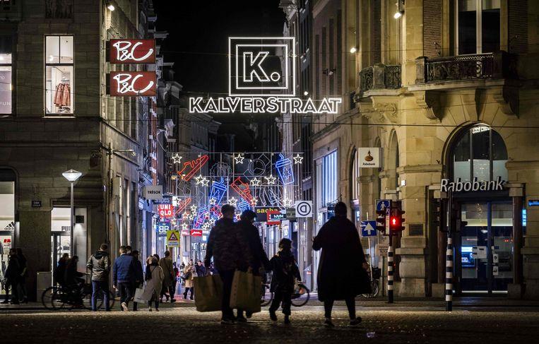 Shoppen in de Kalverstraat in Amsterdam. De winkels zijn nooit dichtgegaan in Nederland. Beeld AFP