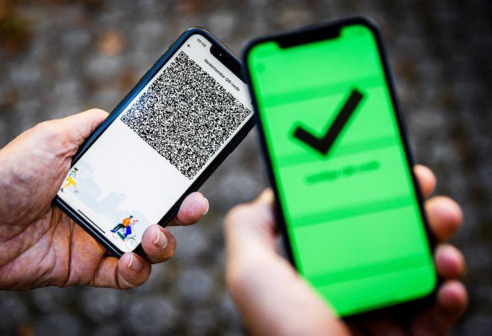 Een telefoon met een groen vinkje in de CoronaCheck app. Op maatschappelijk vlak is discussie ontstaan over het deurbeleid bij niet-gevaccineerden tegen het coronavirus.