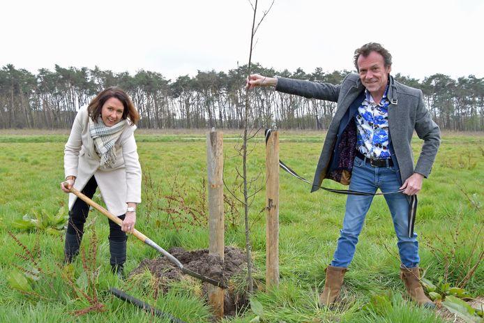 Gedeputeerde Anita Pijpelink en wethouder Gino Depauw planten een boom op een nieuw verworven akker in de Clingepolder.