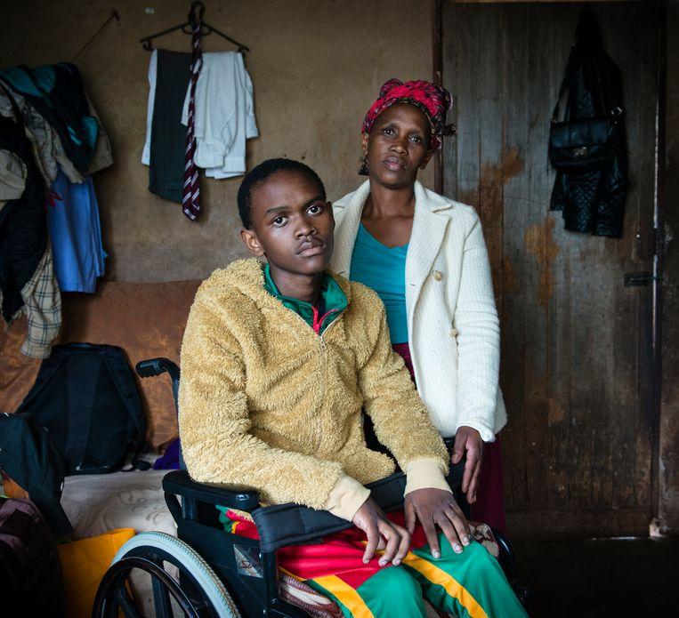 De door kogels verlamde Machawe Lukhuleni samen met zijn moeder Thembile Groening in hun huisje in Lomahasha in Eswatini  Beeld Bram Lammers