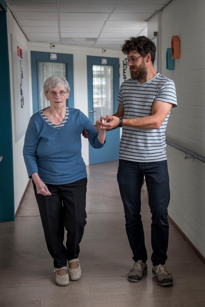 Alexander Kors wandelt met een patiënt door de gang: ,,Opdrachten kun je meteen in de praktijk uitvoeren.''