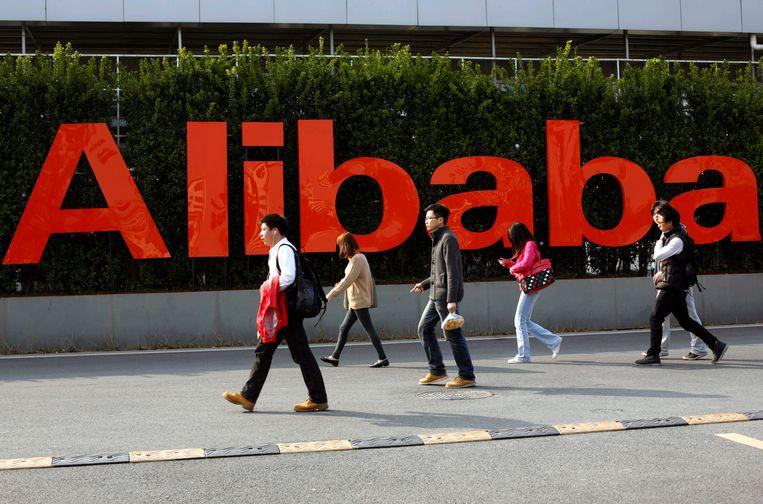 Werknemers van de Chinese e-commercegigant Alibaba lopen op het terrein van het hoofdkwartier van de onderneming in Hangzhou.  Beeld EPA