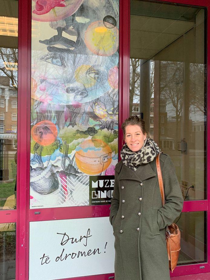 Ingrid Friesen bij de raamsticker die van haar werk is gemaakt.