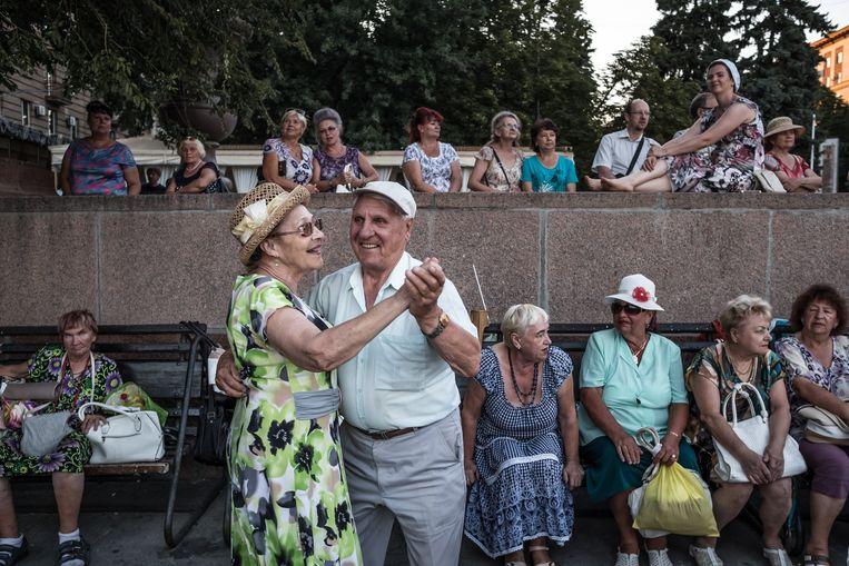Pensionado's dansen op straat in Volgograd. Russische gepensioneerden krijgen gemiddeld 178 euro per maand van het pensioenfonds. Beeld Sergey Ponomarev