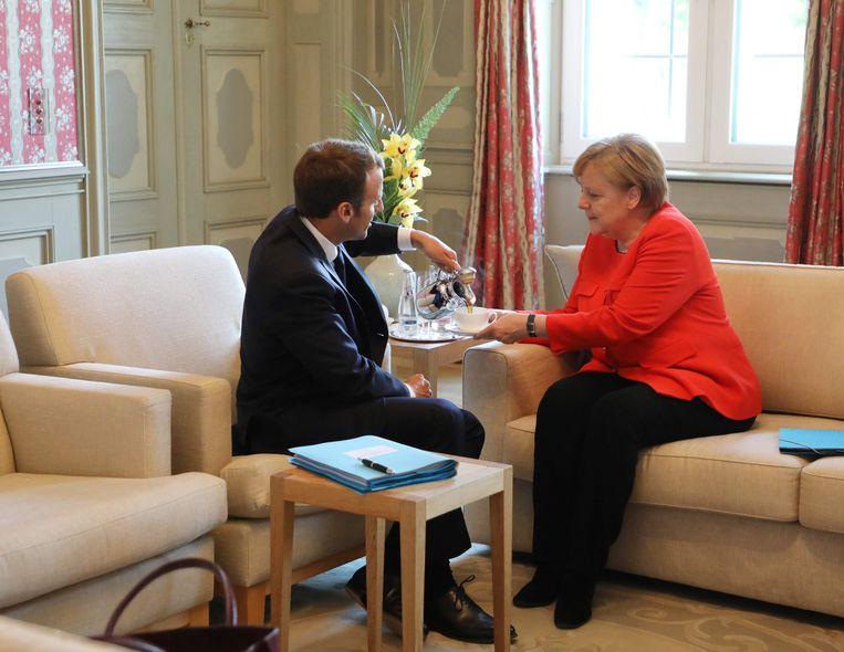 Macron schenkt Merkel een kop koffie in, juni 2018. Beeld AFP