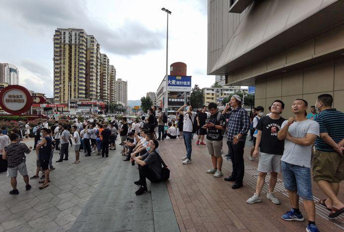 Mensen buiten aan de SEG Plaza nadat de wolkenkrabber op 18 mei plots begon te schudden.
