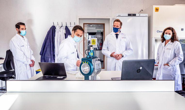 Minister Hugo de Jonge (tweede van rechts) en burgemeester Femke Halsema krijgen donderdag uitleg in Amsterdam-Zuidoost over een nieuwe sneltest voor covid-19. Beeld Raymond Rutting / de Volkskrant