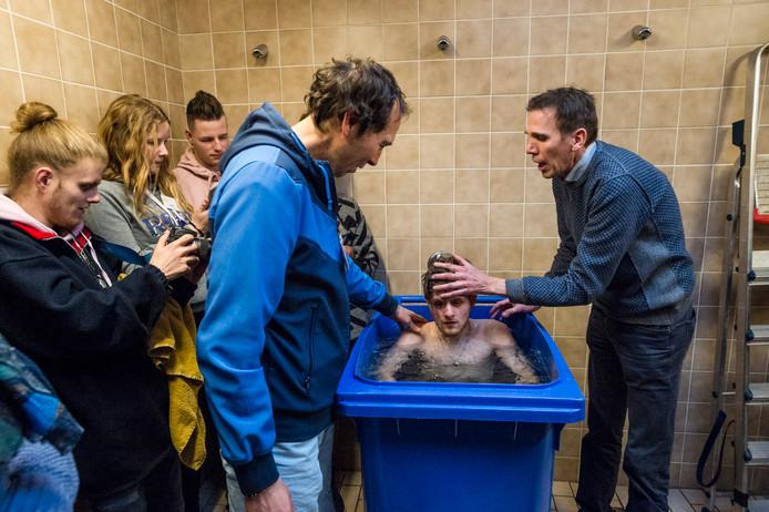 In de doucheruimte van de sporthal  wordt Jesper Lotsy in een container gedoopt.