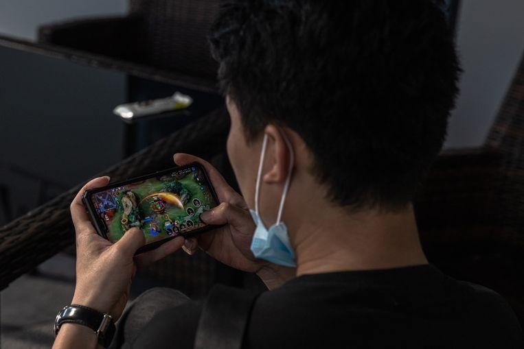 Een Chinese jongeman speelt het populaire spel Honor of Kings op zijn smartphone. Beeld EPA