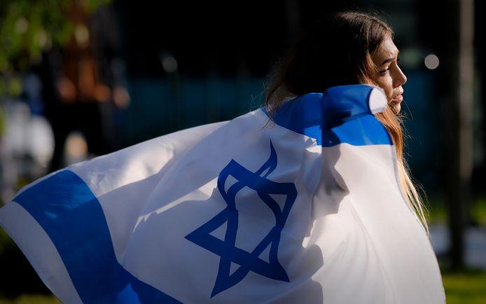 Een vrouw wandelt met een vlag van Israël bij een protest tegen het geweld in het land.