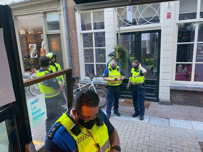 Bij café Lalalaa geven agenten en boa's boetes voor het overschrijden van coronaregels.