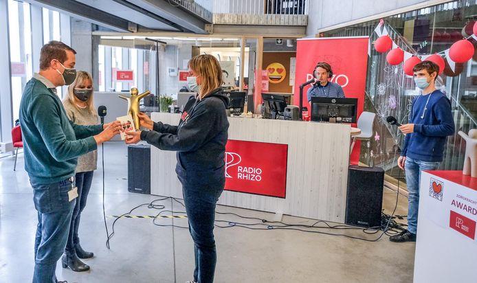 Leerkracht Kim Hellin bedankt twee zorgmedewerkers van AZ Groeninge met een Zorgkracht Award.