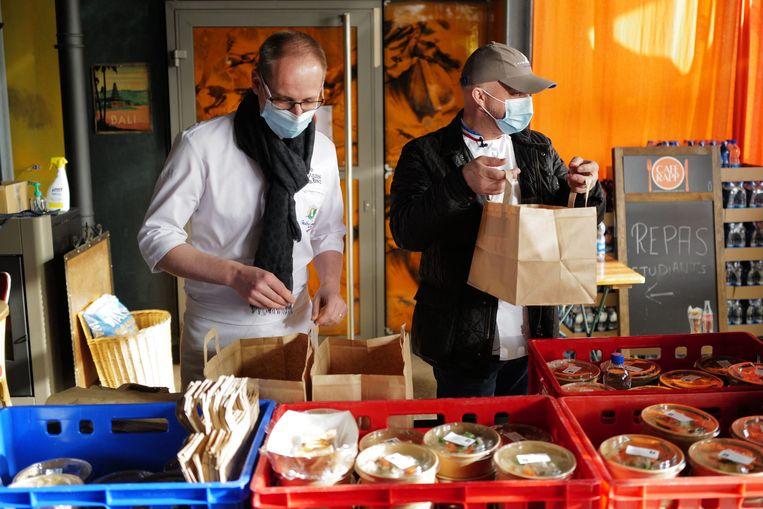 De Franse tweesterren-chef Oliver Nasti bereid afhaalmaaltijden voor.  Beeld AFP